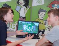 Zwei Jugendliche besprechen Computerspiel vor Laptop