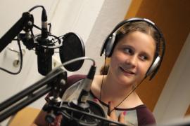 Mädchen im Hörfunkstudio vor Mikrofon, lächelnd
