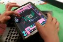 Kind mit Tablet, darauf zu sehen die selbsterstellte Spielfigur