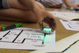 Zu sehen ist ein Kind, das mit großem Vorlagenbogen, Roboter und Stiften arbeitet.