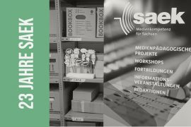 """Abschiedsbild für das Projekt SAEK. Zu sehen sind Kisten im Archivregal und das Rollup in Grautönen und ein grüner Schriftbalken mit dem Titel """"23 Jahre SAEK"""""""